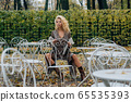 Young blond girl sitting at table in public park 65535393