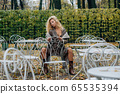 Young blond girl sitting at table in public park 65535394
