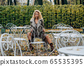 Young blond girl sitting at table in public park 65535395