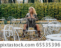 Young blond girl sitting at table in public park 65535396