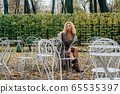 Young blond girl sitting at table in public park 65535397