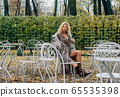 Young blond girl sitting at table in public park 65535398