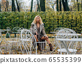 Young blond girl sitting at table in public park 65535399