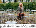 Young blond girl sitting at table in public park 65535400