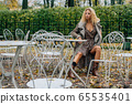 Young blond girl sitting at table in public park 65535401