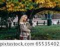 Young blond girl with closed eyes staying near 65535402