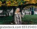Young blond girl walking in public park in fall 65535403