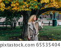 Young blond girl walking in public park in fall 65535404