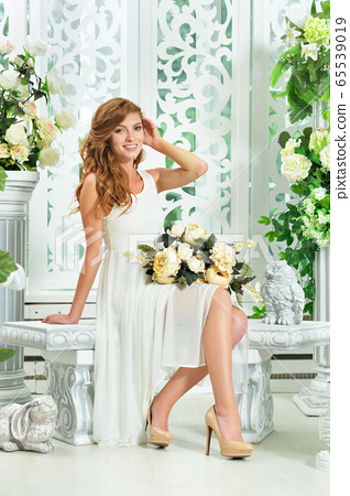 Beautiful young woman posing in room decorated with white flowers 65539019