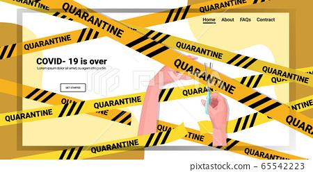 human hand holding scissors and cutting yellow tape coronavirus quarantine is over 65542223