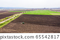 Agricultural industrial tractor plows soil field 65542817