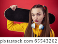 Teen colorful female with headphones and skateboard 65543202