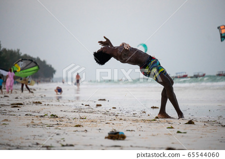 Young Attractive Muscular and Strong Athletic Black African Man at the White Sand Beach Training Body Calisthenics 65544060