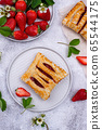 Sweet puff pastry cakes with strawberry 65544175