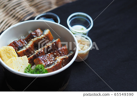 Side view of Unadon or unagi donburi or eel bowl is a dish originating in Japan on black background. 65549390