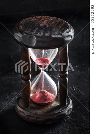 Time is running out concept. An hourglass with sand falling through, on a black background 65552392