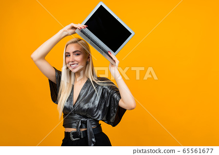smiling young woman holding a laptop with a blank screen to insert a web page on a yellow studio background 65561677