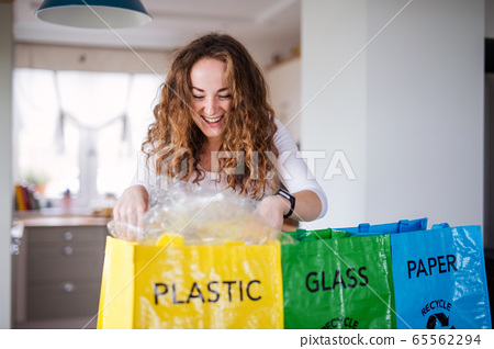 Young woman indoors at home separating glass, paper, and plastic waste. 65562294