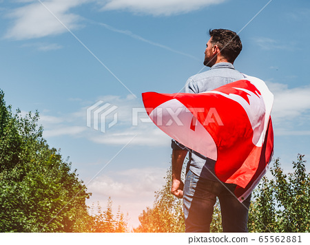 Attractive man holding Canadian Flag. National 65562881