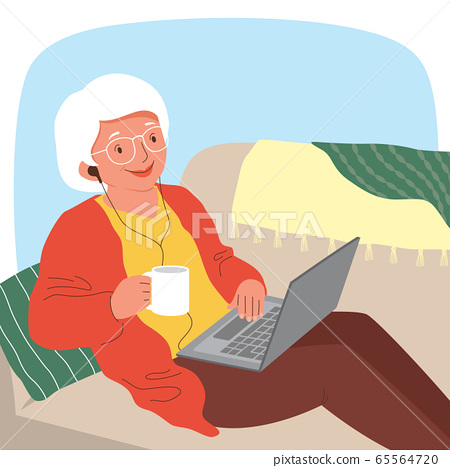 Senior woman using a laptop with earphones while relaxing on the sofa.   65564720