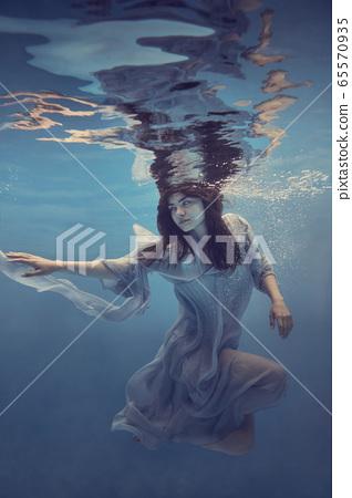 Portrait of a girl in a blue dress under water 65570935