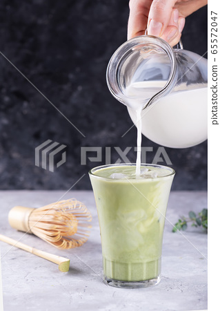 A milk is pouring into a glass with matcha tea on gray table for drink preparation 65572047