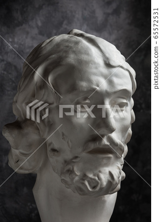Gypsum copy of ancient statue John the Baptist head on dark textured background. Plaster sculpture man face. 65572531
