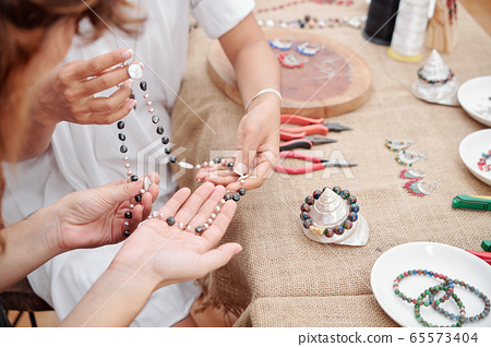 Women making jewelry at home 65573404