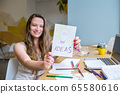 Blurred smiling woman holding a focused sheet with 65580616