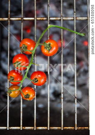 Branch with cherry tomatoes cook on the grill on an open fire, top view 65588098