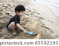 一个男孩在海滨的沙子里建造一座城堡 65592193
