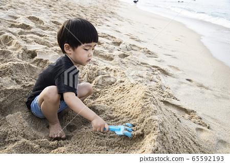 一個男孩在海濱的沙子裡建造一座城堡 65592193