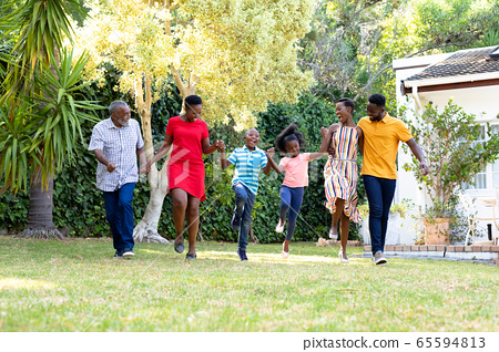 Three generation African American family spending time together in their garden. 65594813