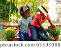 African American girl and her mother planting flowers. 65595088