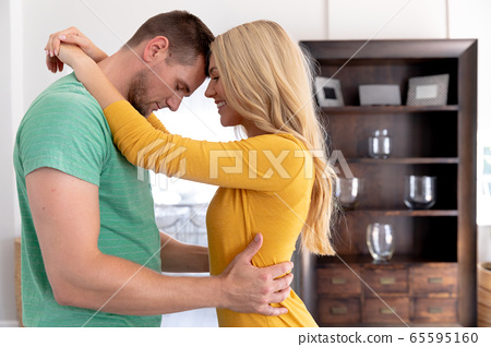 Caucasian couple smiling and embracing at home 65595160
