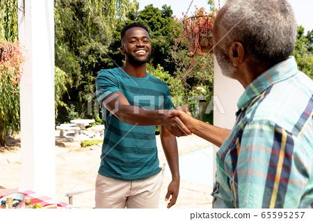 Senior African American man holding hands with his son during a family lunch in the garden 65595257