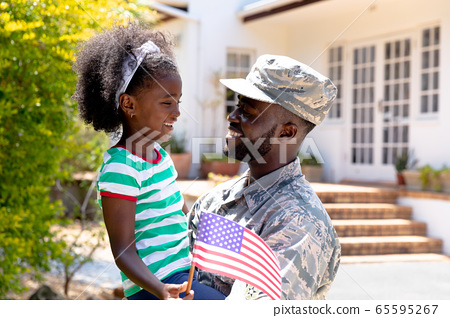 African American male soldier holding his daughter with a US flag in his arms 65595267