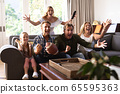 Multi-generation Caucasian family sitting on a couch together and watching a game 65595363