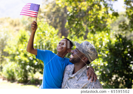 African American man wearing a military uniform holding his son 65595502
