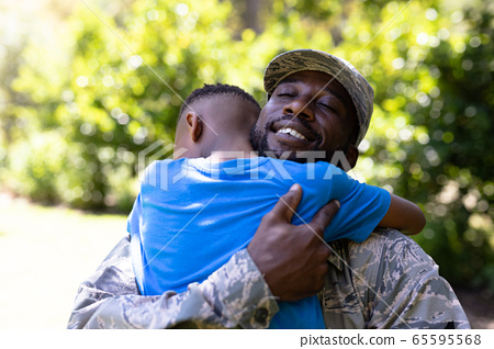 African American man wearing a military uniform holding his son 65595568