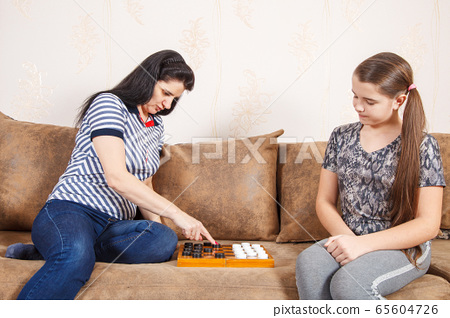 mom and daughter play checkers at home 65604726