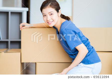 Beautiful woman, moving house 65611094