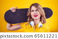 Cheerful young woman with skateboard 65611221