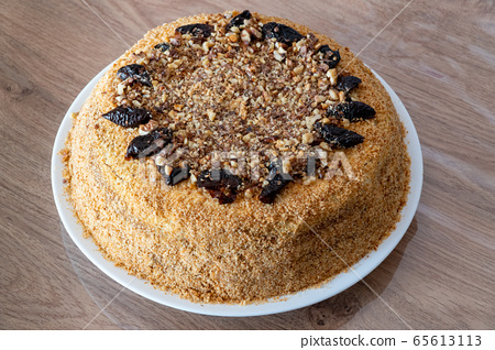 Delicious cake with prunes and sprinkled grated nuts. Home baked 65613113