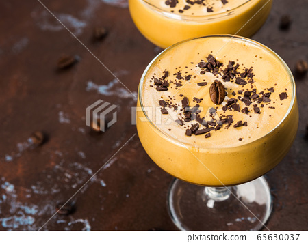 Frappe coffee in dessert glasses on brown backdrop 65630037