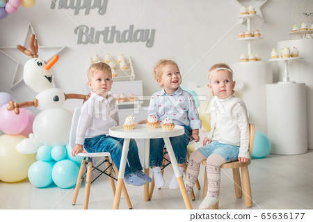 Cute little boys and girl at a table with birthday cakes at a children's party with balloons. Children's party. Balloons 65636177