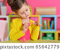 Little girl with stylish hairstyle wearing yellow jacket doing manicure at home 65642779