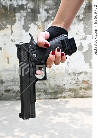 Female hand holding pistol in front of cement wall 65669752