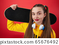 Teen colorful female with headphones and skateboard 65676492