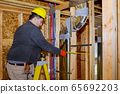 Male builder installing ventilation pipes with new 65692203